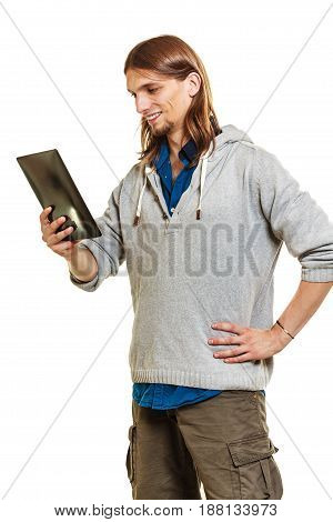 Young fashionable man using computer tablet browsing surfing the internet. Fashion and modern technology.