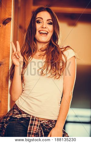 Happy cute pretty gorgeous woman at home. Attractive young girl with long hair wearing white shirt and jeans showing peace sign gesture. Instagram filter.