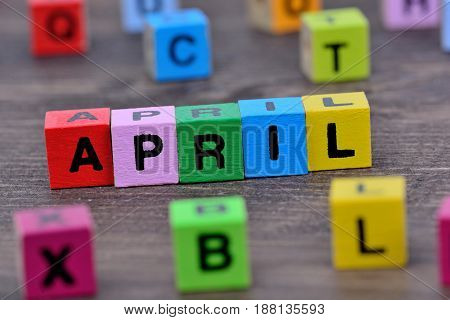 April word on wooden table close up