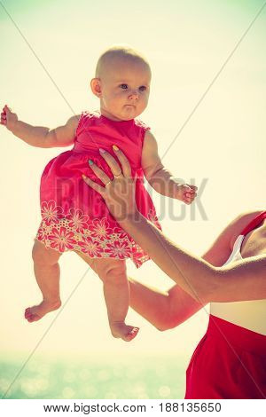 Small child in the arms of his mother flying sky and water in the background.