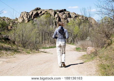 Woman Hiker Is Walking To The Rocks. White Road, Bushes And Trees, Springtime
