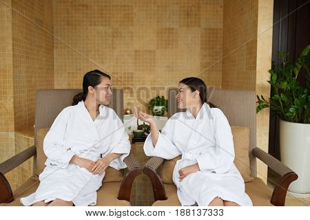 Best friends in bathrobes having wellness weekend: they sitting on lounge chairs and chatting with each other while waiting for beginning of rejuvenation procedure