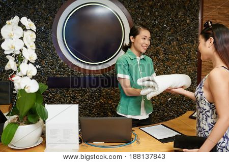Attractive young receptionist with friendly smile giving terry towel to female client of spa center, waist-up portrait
