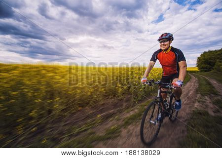 A male cyclist is riding on a picturesque yellow rapeseed field. Sports, active recreation.