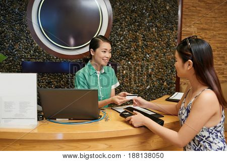 Young female client paying for treatment procedure with credit card at luxurious spa salon, waist-up portrait
