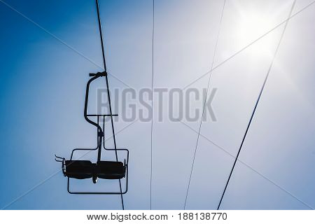 Silhouette Of Ski Lift With Blue Sky And Sun On The Background