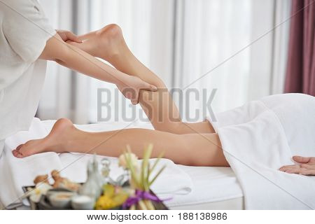 Profile view of unrecognizable client being massaged while lying on table at luxurious spa salon
