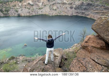 Female Is Standing On The Big Stone Abobe The Blue Lake. Rocky Screes On The Banks. Spreads Her Arms