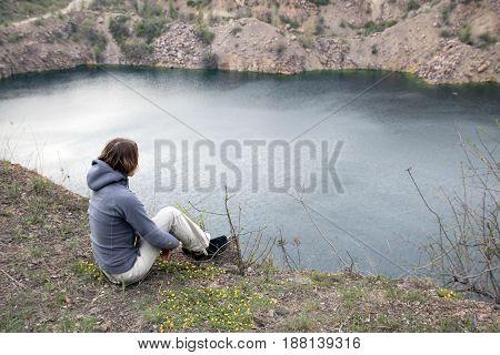 Female Sits On The Big Stone Abobe The Blue Lake. Rocky Screes On The Banks. Hugs Her Legs