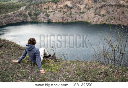 Girl Sits On The Edge Of The Cliff Abobe The Blue Lake. Rocky Screes On The Banks.