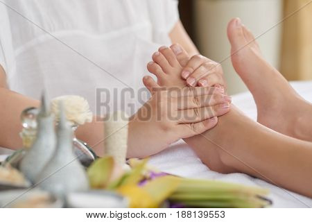 Unrecognizable woman easing muscle tension with help of foot massage at spa salon, close-up shot