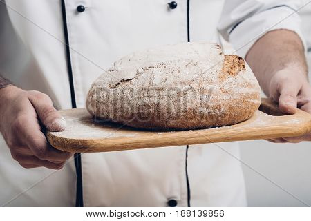 Fresh baked bread  on a wooden board in the hands of a baker. soft light