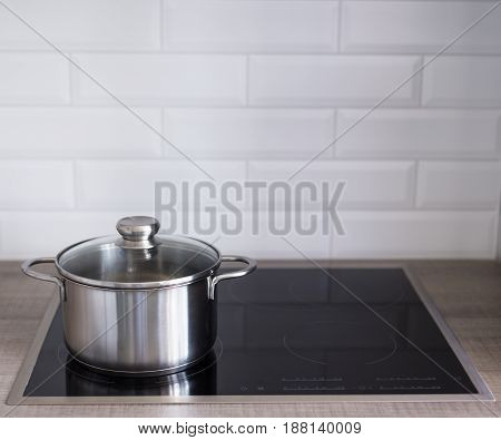Close Up Of Metal Pot On Electric Or Induction Stove In Kitchen