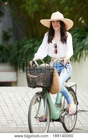 Attractive woman with charming smile enjoying sunny day while riding bicycle in park, full length portrait
