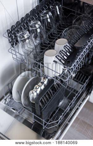 Open Dishwasher With Clean Utensils In Kitchen