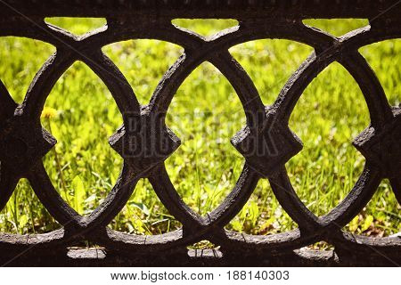 Old black cast fence on a green lawn background. Antique wrought iron fence with ornamental pattern of circles