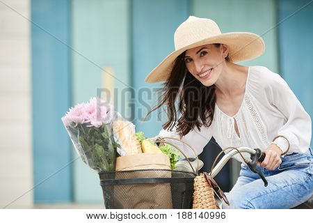 Portrait of middle-aged woman looking at camera with wide smile while sitting on bicycle after shopping for groceries