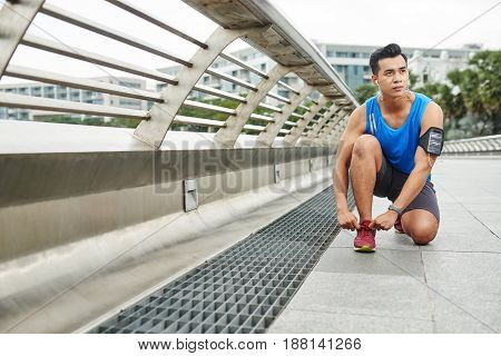 Full-length portrait of handsome sporty man tying his shoelaces before intensive outdoor training