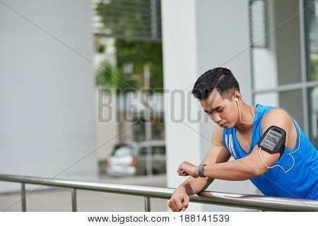 Waist-up portrait of pensive Vietnamese man checking his heart rate on fitness tracker after intensive outdoor training