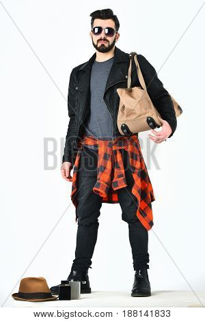 Bearded man short beard. Caucasian hipster with moustache holding casual stylish bag wearing black leather jacket checkered red shirt and ripped jeans isolated on white background