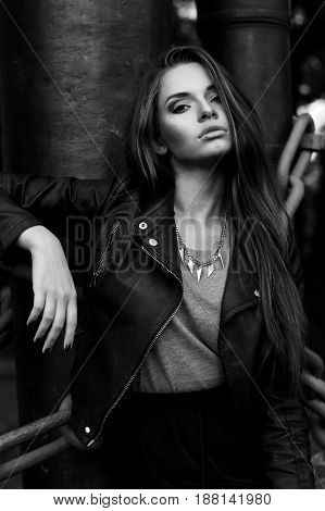 outdoor stylish fashion portrait. young beautiful girl with long hair wearing black clothes. black leather jacket and skirt