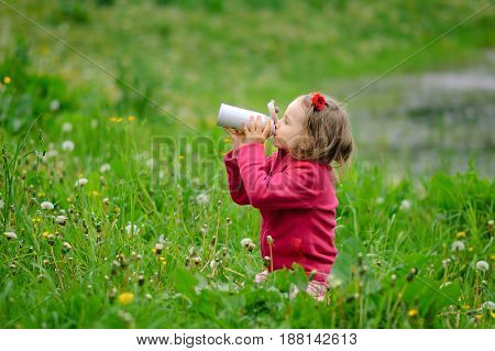 The girl drinks water from a thermos bottle. Mug-thermos, spring grass, curly hair, outdoor recreation, healthy lifestyle, environmental protection, protection of nature, conscious consumption.