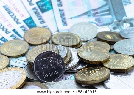 Russian coin one ruble on the background of banknotes