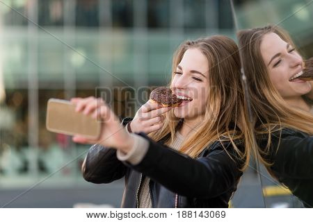 Young woman taking selfie with phone while eating chocolate donut in street