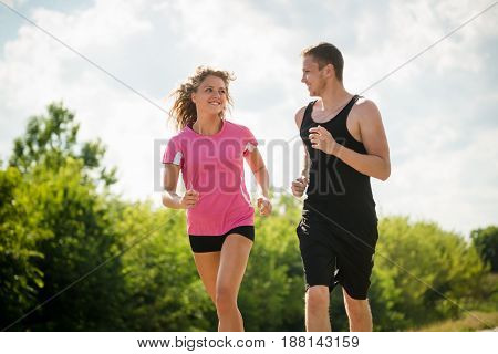 Fitness couple jogging together, healthy lifestyle. Nature background.