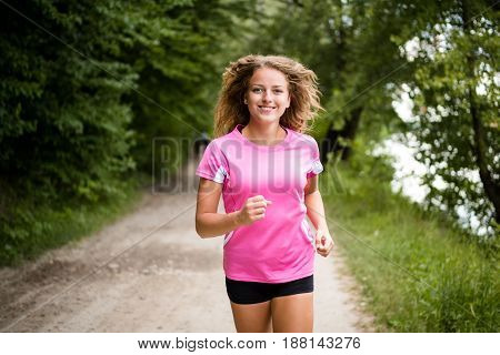 Smiling fitness model jogging through the forest trail