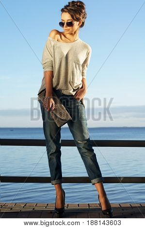 beautiful girl standing against blue sea and sky and looking at you. Young stylish woman in pullover and jeans with handbag. Summer outdoor fashion portrait.