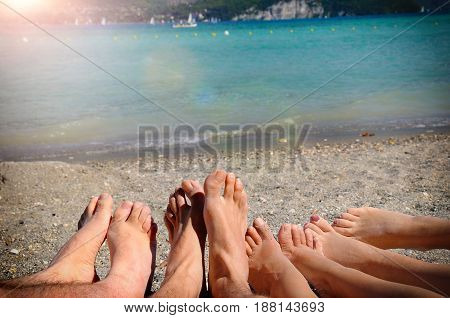 Funny Tourism Concept With Feet Of Tourists Lying On Sand