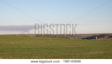 green field, smoke on the horizon, water pump house in the right corner, blue sky, sunset