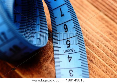 Tape For Measuring In Blue Color On Vintage Wooden Background