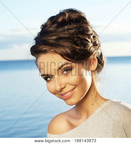 Pretty smiling young woman portrait against blue sea and sky. Stylish girl with hairdress.