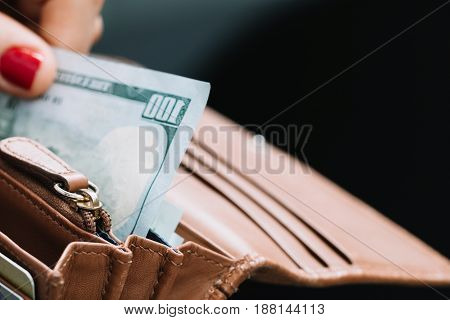The girl's hand takes out paper dollars from a leather orange purse. Crisis and economy concept. Close-up.