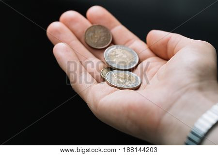 Close-up of euro coins in the palm on a dark background. Crisis and economy concept.