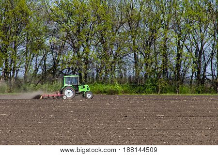 The tractor cultivating the field on spring