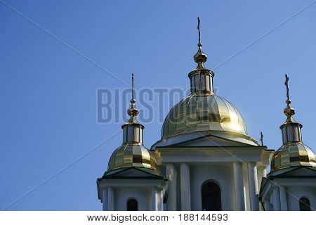 Glittering domes of a Christian Church on the background of blue cloudless sky