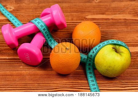 weight loss concept dumbbells weight with measuring tape orange and apple fruit on brown vintage wooden background
