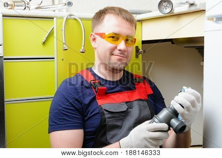 Plumber In The Kitchen Repairing The Water Pipe