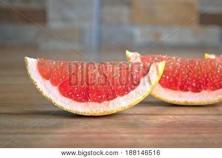 Closeup of red grapefruit wedges on a wooden table