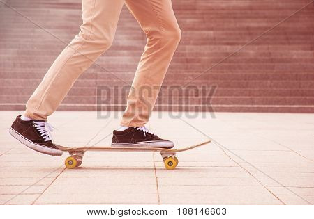Desperate skateboarder performs dangerous movement on the skateboard at sunset