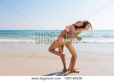 Two young asian brunette best friends looking on camera and sending you air kiss have sexy slim body wearing bikini sunglasses and fashion bright jewelry posing in front of tropical beach.
