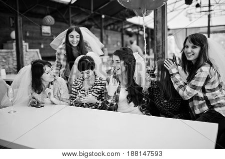 Group Of Cheerful Girls At Checkered Shirts Sitting At Table On Hen Party. Girl Showing Her Engageme