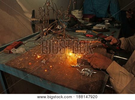 Welder working in workshop in the dark in University of Karachi Karachi Pakistan 04/10/2011