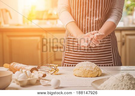 Woman slap his hands above dough closeup. Baker finishing his bakery, shake flour from his hands, free space for text. Homemade bakery, cooking process concept
