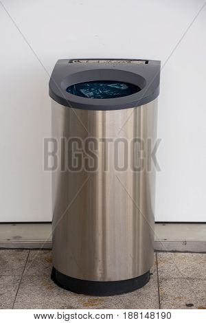 Dustbin with ashtray in front of a white wall