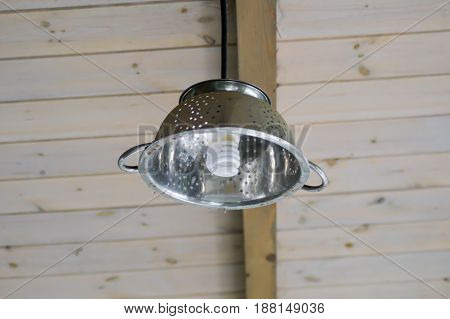 Hanging light in the form of a paste strainer