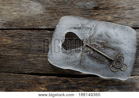 Old key in a block of ice with a heart on the old boards